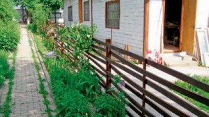 Wooden decorative fence for the garden at the cottage photo, fence of wood with their hands for the flower beds and vegetable garden
